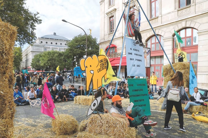 PARIS: A woman sits on a high hammock as protesters block the road with hay bales and signs during a demonstration called by Extinction Rebellion on Monday.—AFP