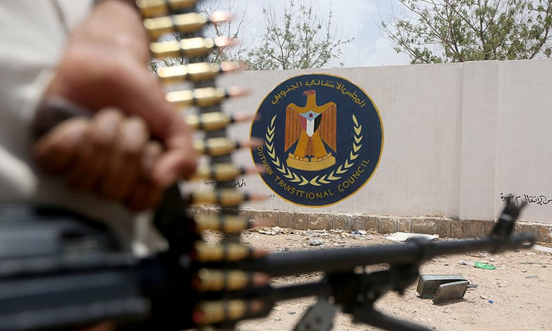 A Yemeni government soldier holds a weapon as he stands by an emblem of the STC at the headquarters of the separatist Southern Transitional Council in Ataq, Yemen on August 27. — Reuters
