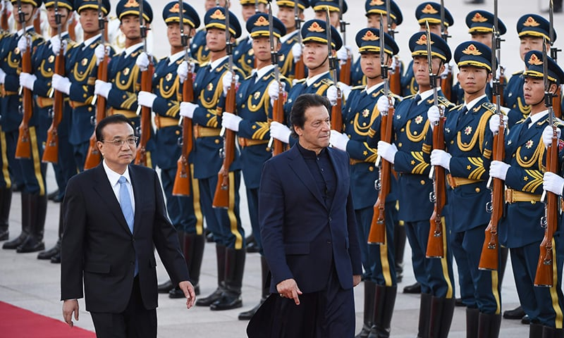 PM Imran Khan reviews a military honour guard with Chinese Premier Li Keqiang during a welcome ceremony outside the Great Hall of the People in Beijing. — AFP