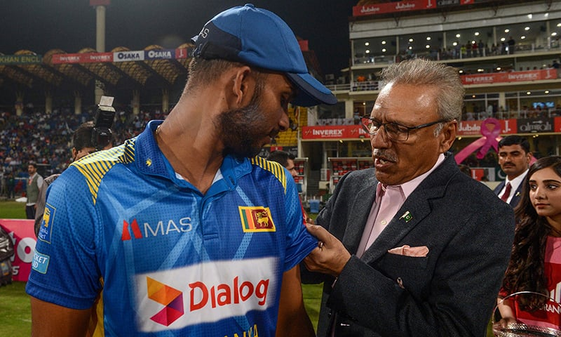 President Arif Alvi puts a pink ribbon on the T-shirt of Sri Lanka's captain Dasun Shanaka ahead of the beginning of the match. — AFP