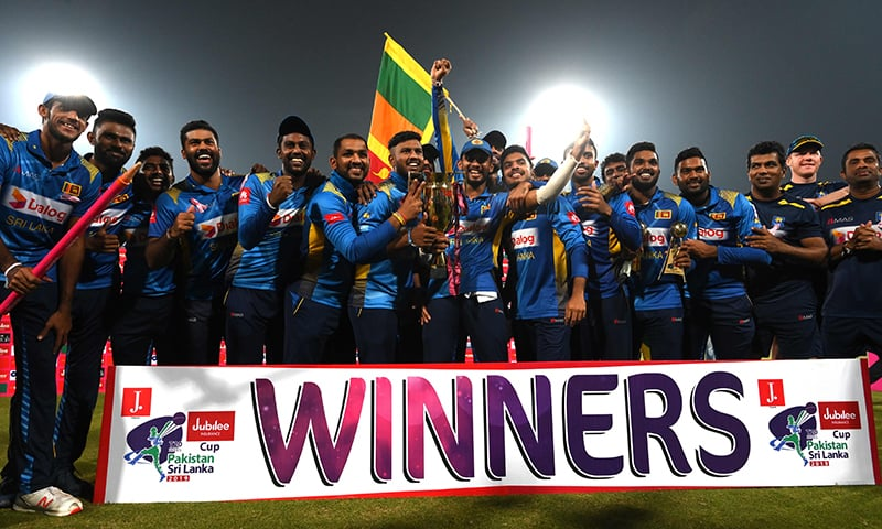Sri Lanka's cricketers pose for a photograph with winning trophy during the third and final Twenty20 International cricket match between Pakistan and Sri Lanka at the Gaddafi Cricket Stadium in Lahore on Wednesday. — AFP