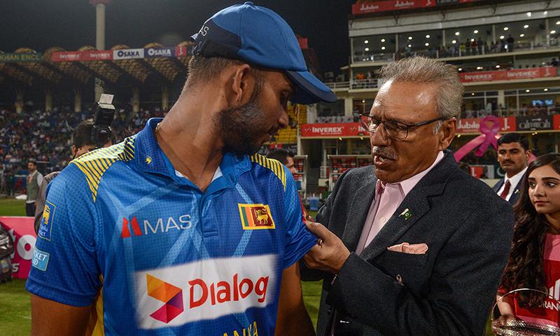 صدر مملکت پنک ڈے کی مناسبت سے سری لنکن کپتان کو گلابی ربن لگا رہے ہیں— فوٹو: اے ایف پی