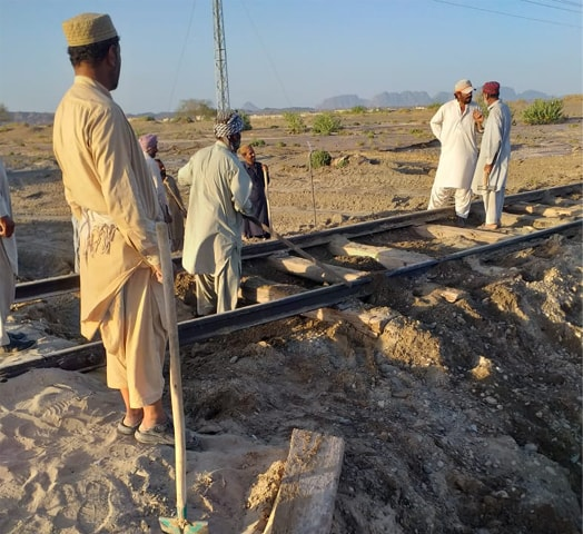 WorkerS are seen with shovels next to a damaged rail track near Dalbandin.—Dawn