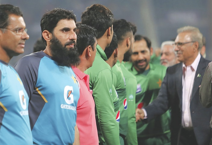 PAKISTAN head coach-cum-chief selector Misbah-ul-Haq (second L) waits to shake hands with President Arif Alvi at the Gaddafi Stadium on Wednesday.—AP