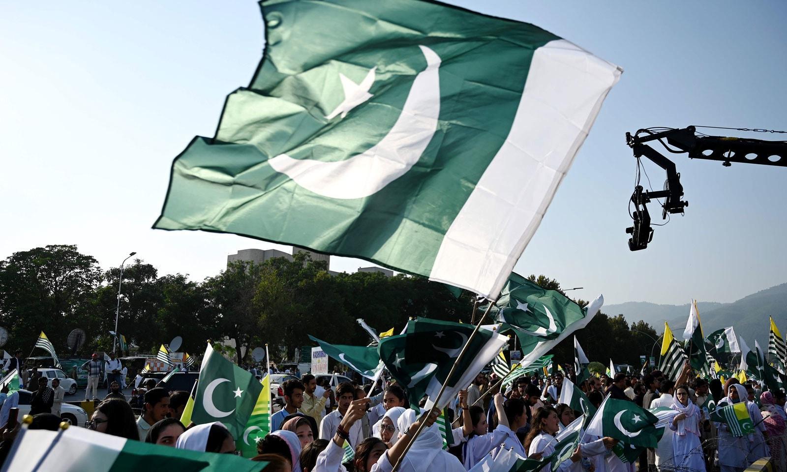 مقبوضہ کشمیر کے عوام سے اظہار یکجہتی کیلئے اسلام آباد میں بنائی گئی انسانی زنجیر میں طلبہ پاکستان اور آزاد کشمیر کے پرچم لہرا رہے  ہیں — فوٹو: اے ایف پی
