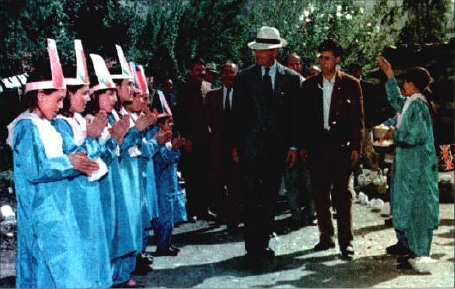 The Duke of Edinburgh, Prince Philip, is showered with petals by Chitrali children at the Aga Khan School in Bilphok on October 10, 1997.