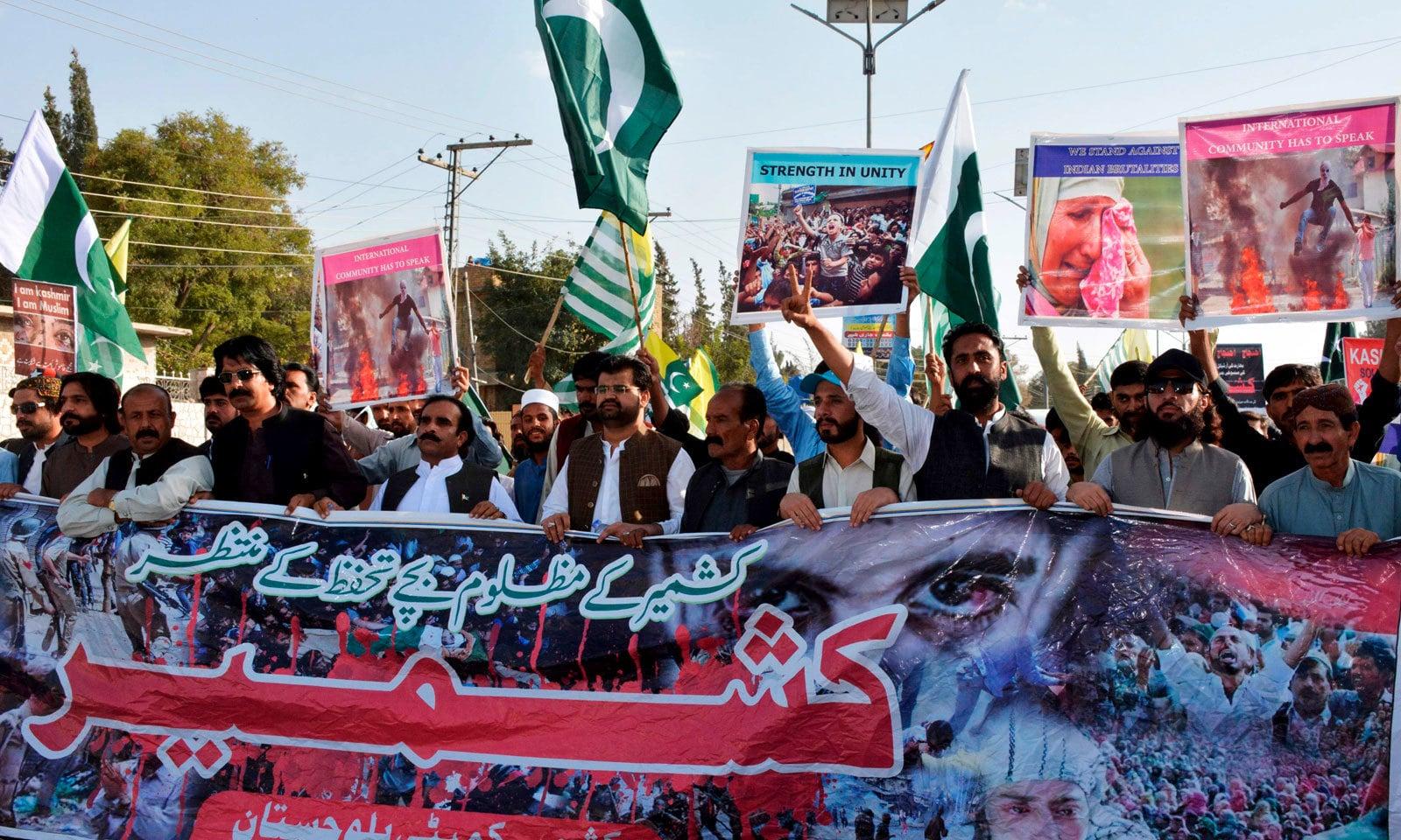 کوئٹہ میں احتجاج کے دوران شرکا نے مقبوضہ کشمیر کے عوام سے اظہار یکجہتی کیلئے پلے کارڈز اٹھا رکھے ہیں — فوٹو: اے ایف پی