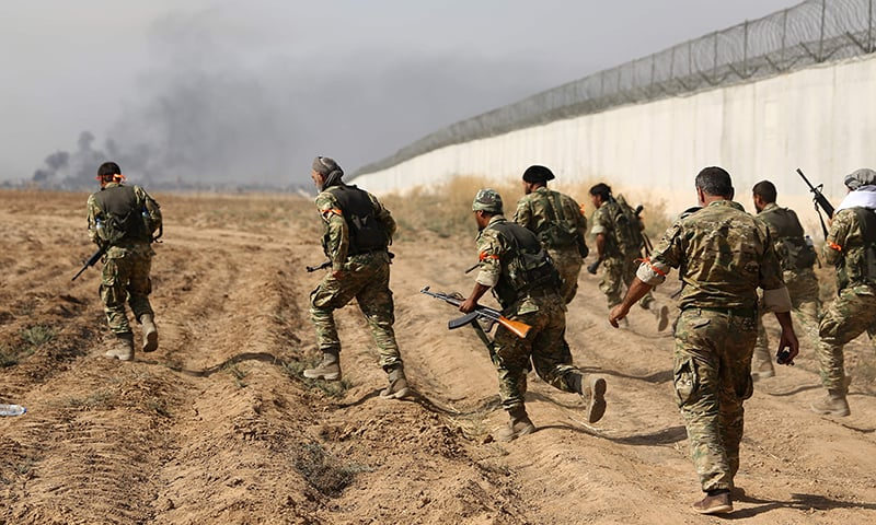 Pro-Turkish Syrian fighters cross the border into Syria as they take part in an offensive against Kurdish-controlled areas in northeastern Syria launched by the Turkish military, on Friday. — AFP