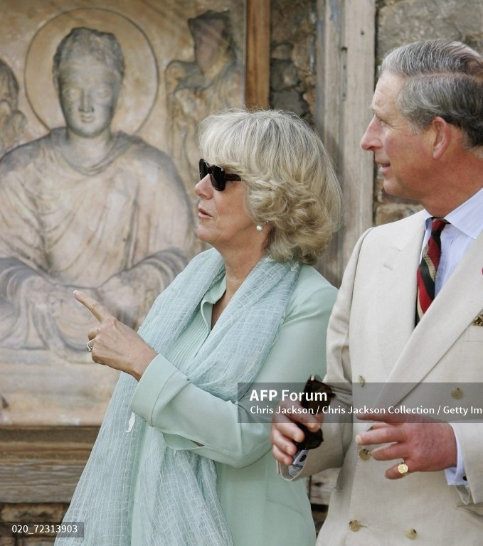 Charles and Camilla walk past a Buddha as they tour Jaulian, a World Heritage archaeological site, on October 31, 2006, in Taxila near Islamabad.