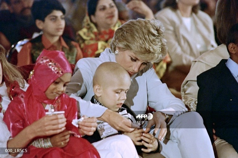 Lady Diana feeds a cancer affected child during the variety show presented by the children at Khanum memorial cancer hospital on February 21, 1996.