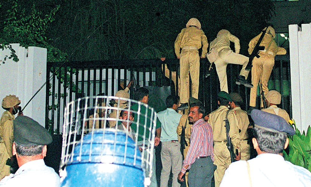 Army men climb over the main gate of the PTV Center in Islamabad on October 12, 1999 .