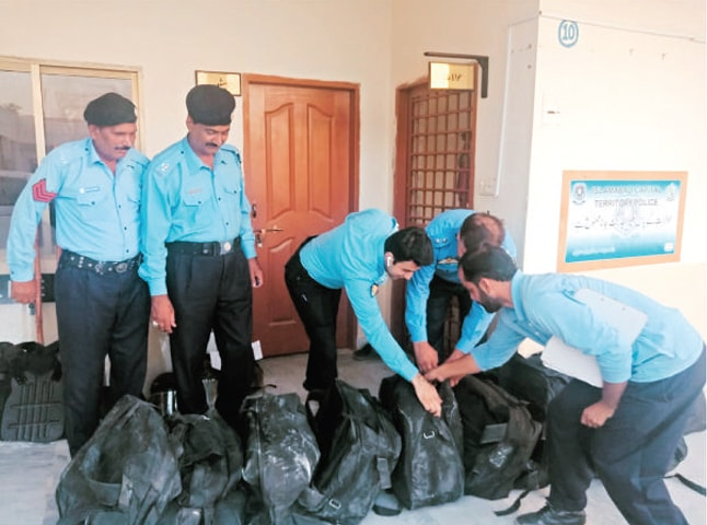 Officials arrange bags containing riot kits at a police station in Islamabad.