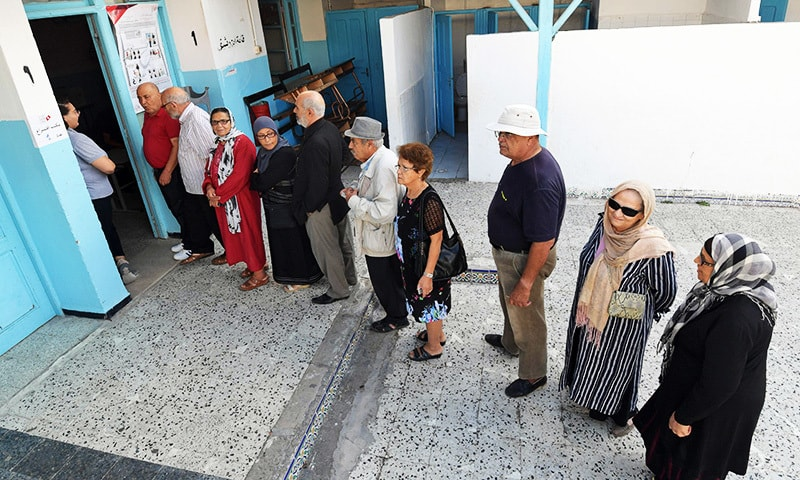 Tunisian voters queue outside a polling station in the capital Tunis on October 13, 2019 during the second round of the presidential election. — AFP