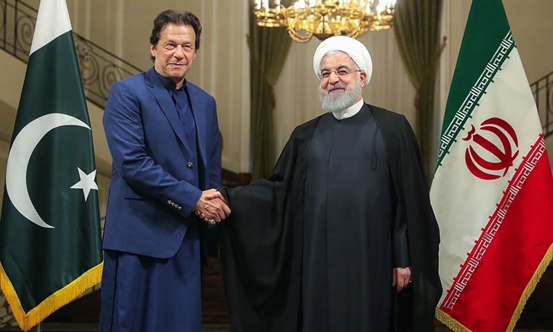 A handout picture provided by the Iranian presidency on Sunday shows Iranian President Hassan Rouhani shaking hands with Prime Minister Imran Khan in the Iranian capital Tehran. — AFP