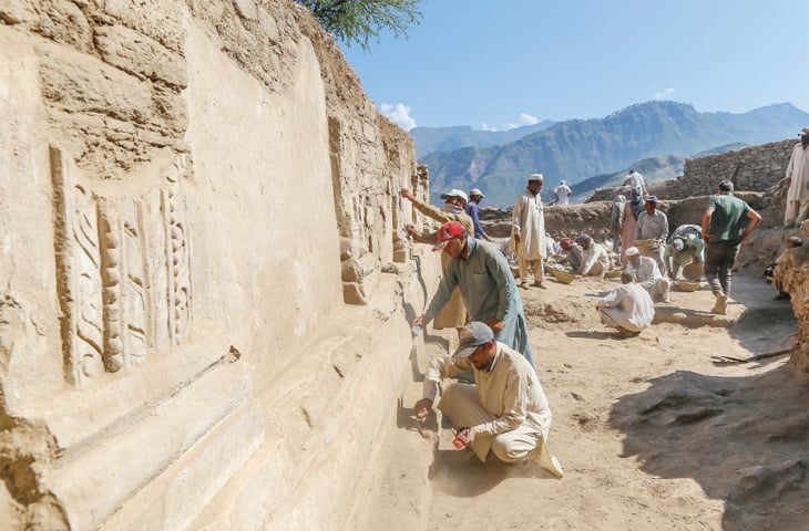 Archaeologists busy in excavation work at the site in Barikot. — Dawn