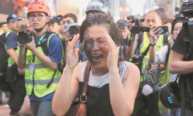 Hong Kong: A woman reacts after protesters sprayed colour on her face for removing road barricades set up  by them.—AP