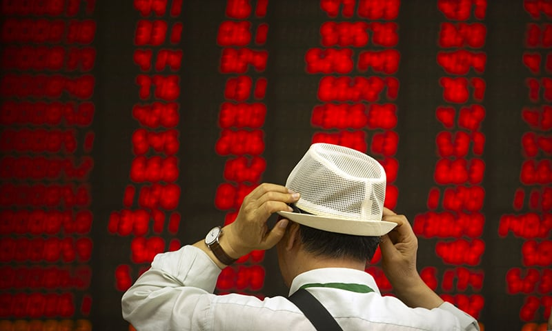 In this September 5, 2019 file photo, an investor adjusts his hat as he monitors stock prices at a brokerage house in Beijing. — AP