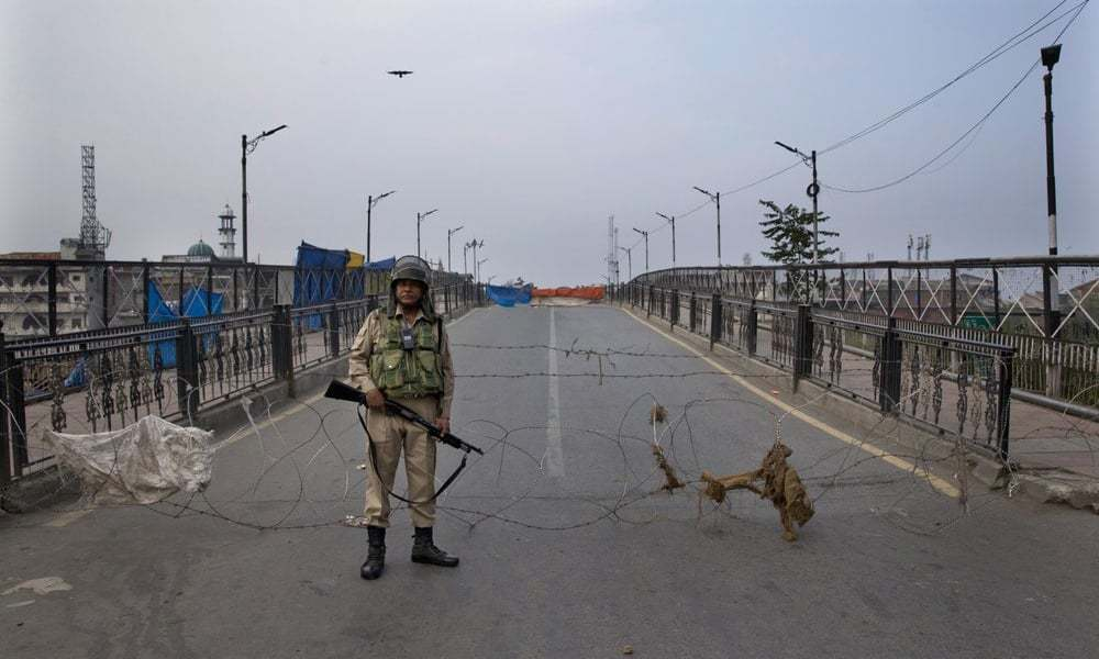 An Indian paramilitary force soldier stands guard near a barbed wire barricade during restrictions in Srinagar  in occupied Kashmir on September 27. — AP/File