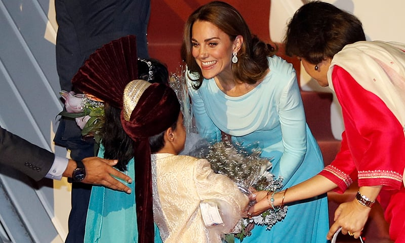 Britain's Catherine, Duchess of Cambridge, receives a bouquet from a child upon arrival in Islamabad on Monday night. — Reuters