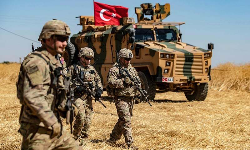 In this photo taken on September 8, 2019, US troops walk past a Turkish military vehicle during a joint patrol with Turkish troops in the Syrian village of al-Hashisha on the outskirts of Tal Abyad town along the border with Turkish troops. — AFP