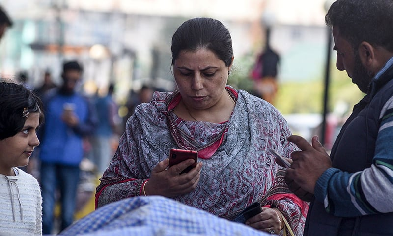 Residents use mobiles phones in Srinagar on October 14 following Indian government's decision to restore mobile phone networks in occupied Kashmir. — AFP