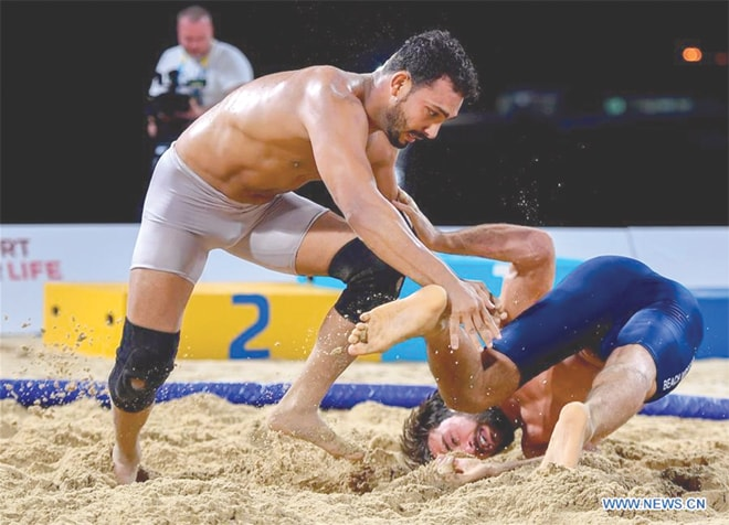 DOHA: Pakistan's Mohammad Inam (L) fights against Dato Marsagishvili of Georgia during the 90kg wrestling final at the ANOC World Beach Games.—Xinhua