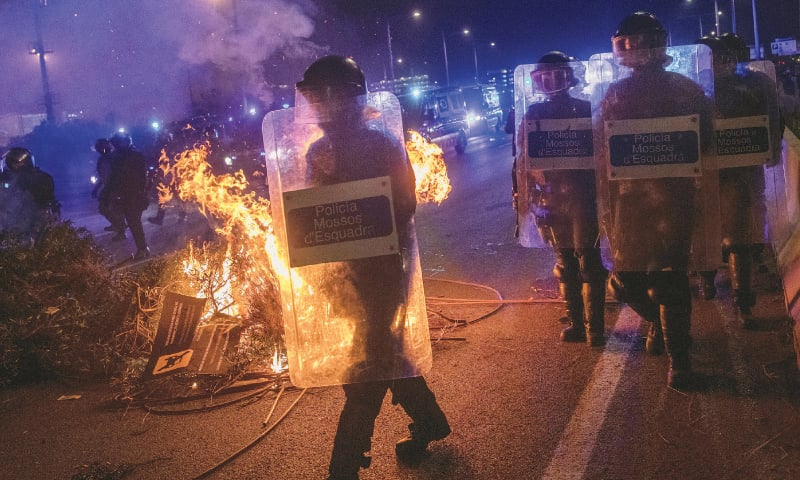 BARCELONA: Riot police units walk past a barricade on fire during a demonstration at El Prat airport, on the outskirts of Barcelona.—AP