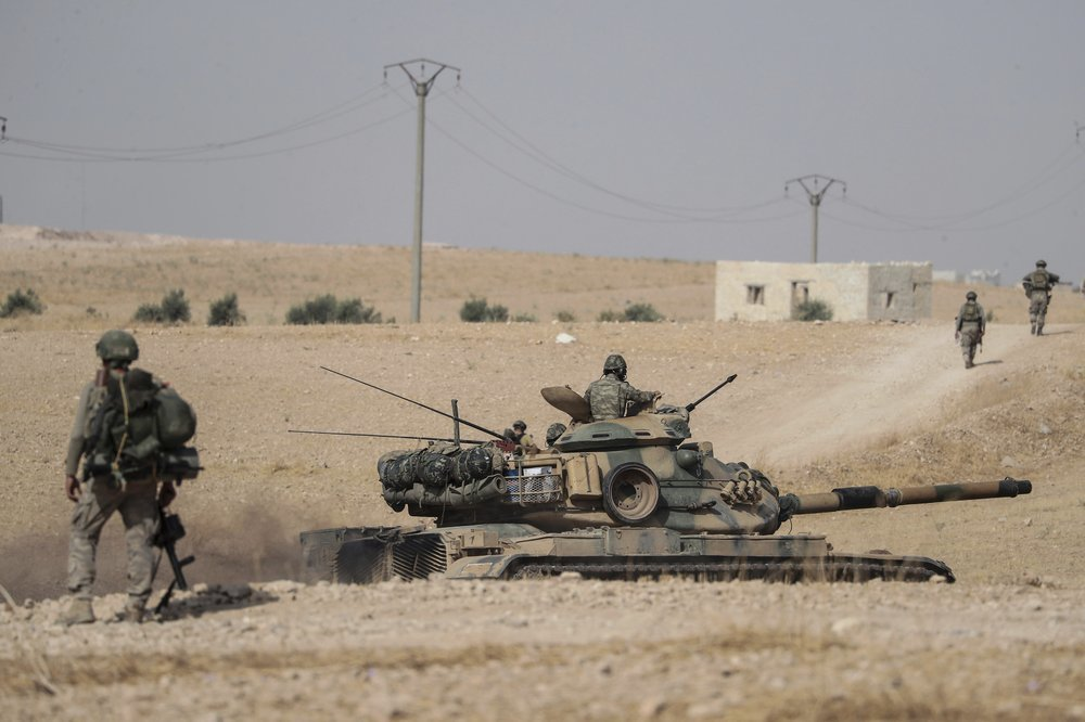 Turkish tanks and troops stationed near Syrian town of Manbij, Syria, on Oct 15. ─ AP