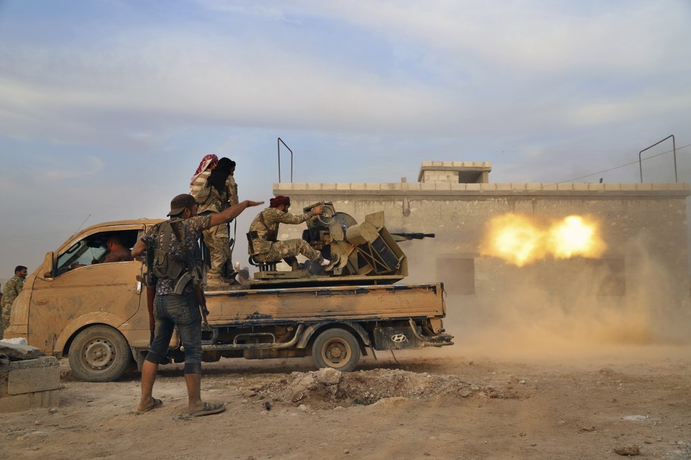 In this Oct 14 photo, Turkey-backed Syrian opposition fighters fire a heavy machine-gun towards Kurdish fighters, in Syria's northern region of Manbij. ─ AP