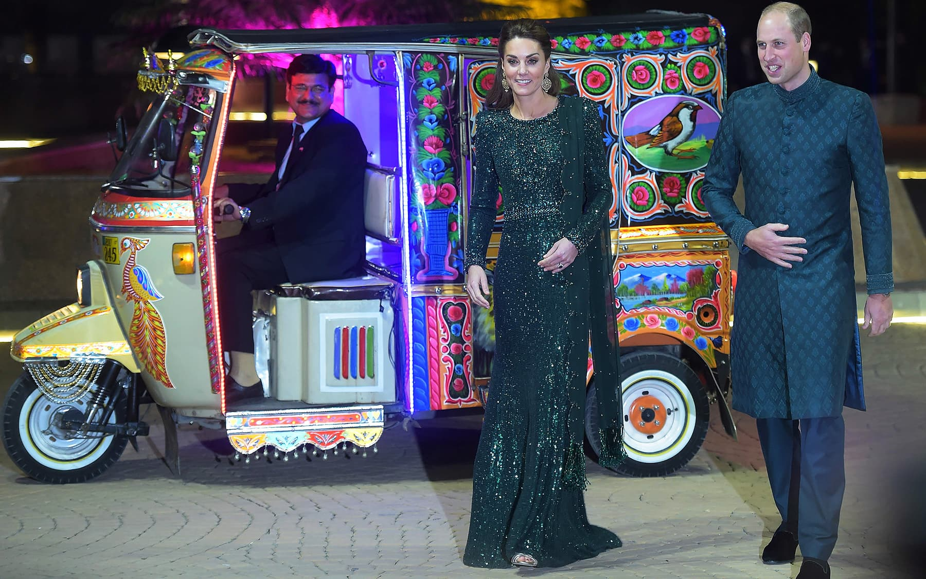 Prince William (R) and his wife Catherine arrive on a decorated auto-rickshaw to attend a reception in Islamabad. — AFP