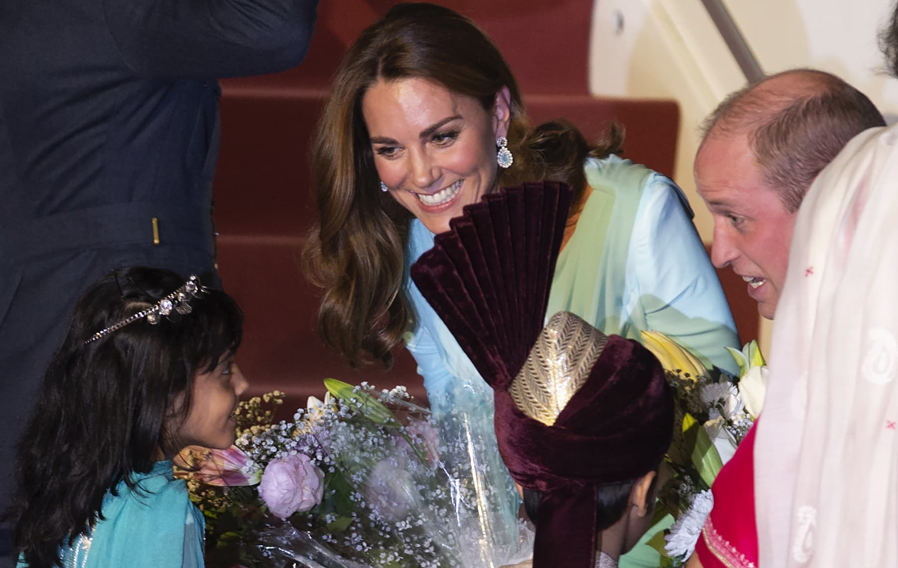 Prince William and his wife Kate receive flowers from a child upon their arrival at the Nur Khan airbase in Islamabad on Monday. — AP