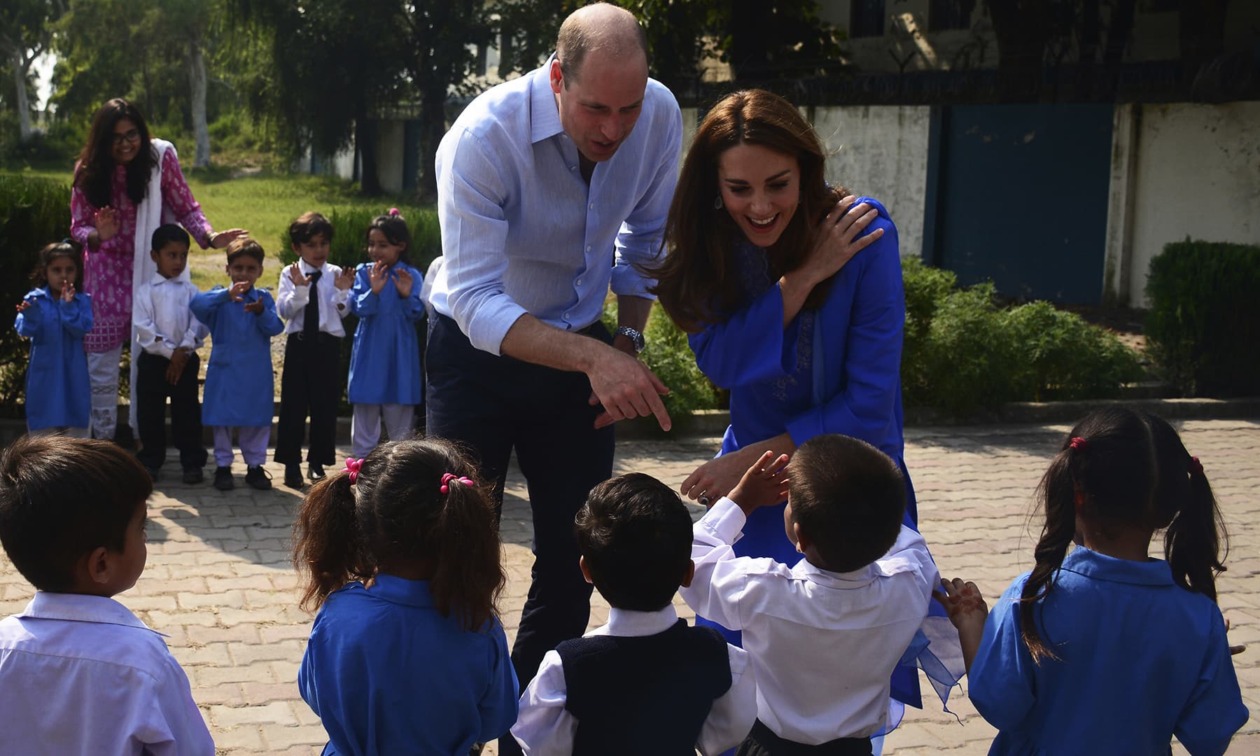 Prince William and his wife Kate interact with students during their visit to a school outside Islamabad ob Tuesday. — AP