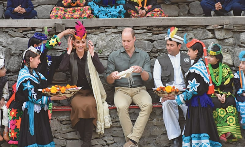 THE Duchess of Cambridge smiles as a Kalasha woman adjusts a Chitrali feathered cap on her head while the Duke prepares to wear his cap.—Dawn