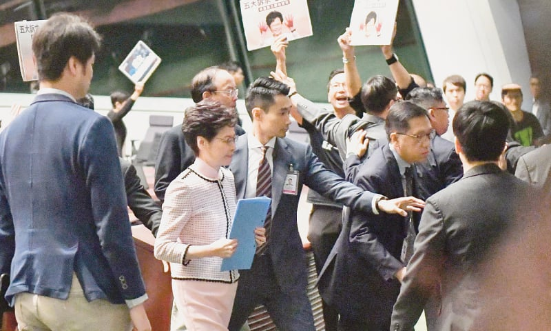 HONG KONG's Chief Executive Carrie Lam (in pink dress) leaves the chamber for a second time while trying to deliver her annual policy address as she is heckled by pro-democracy lawmakers (in the background) at the Legislative Council on Wednesday.—AFP