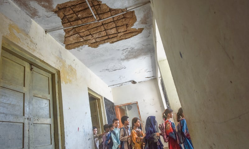 STUDENTS pass under a broken ceiling at the school in Siraj Ahmed  Goth. — Fahim Siddiqi / White Star