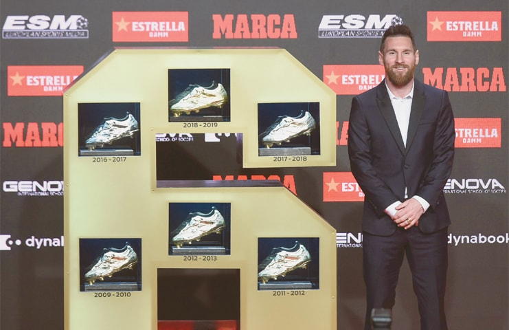 BARCELONA: Barcelona's Lionel Messi poses with his sixth Golden Shoe award at the Antigua Fabrica Estrella Damm on Wednesday.—AFP