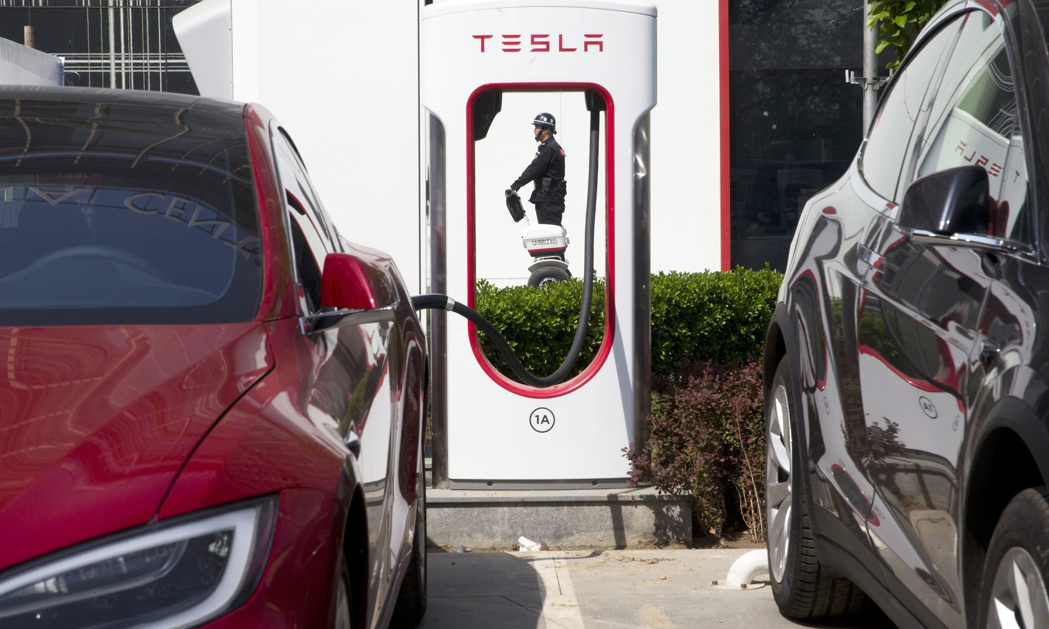 In this April 14, 2017 photo, a security guard moves past Tesla electric vehicle charging station in Beijing. — AP
