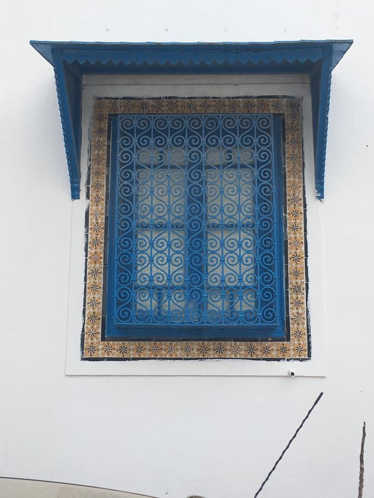 Blue latticework window screens — known as mashrabiya.