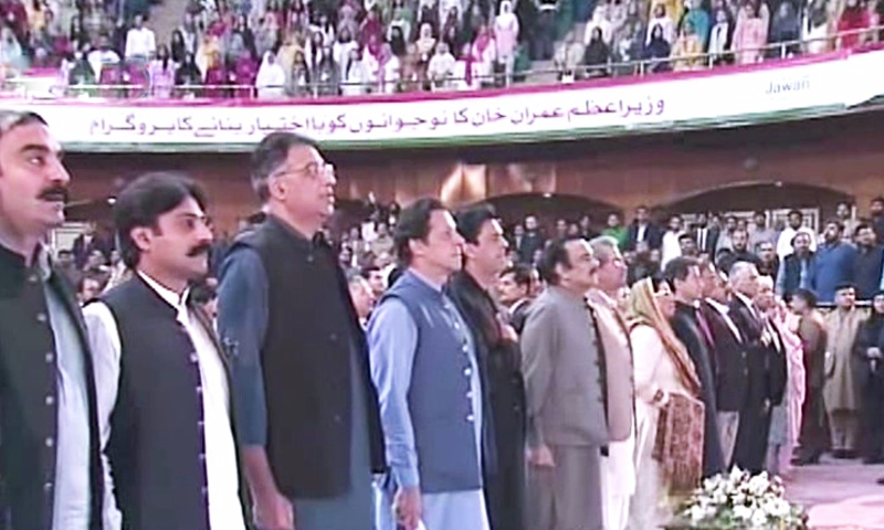 Prime Minister Imran Khan, PTI leaders and participants of the ceremony stand as the national anthem is played. — DawnNewsTV