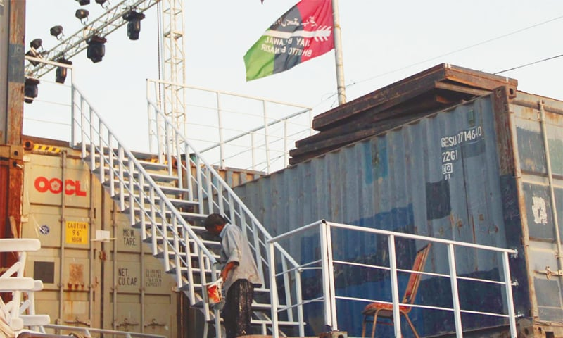 A MAN paints the makeshift stairs of the under-construction stage for PPP's public meeting at the venue on Thursday.—Online