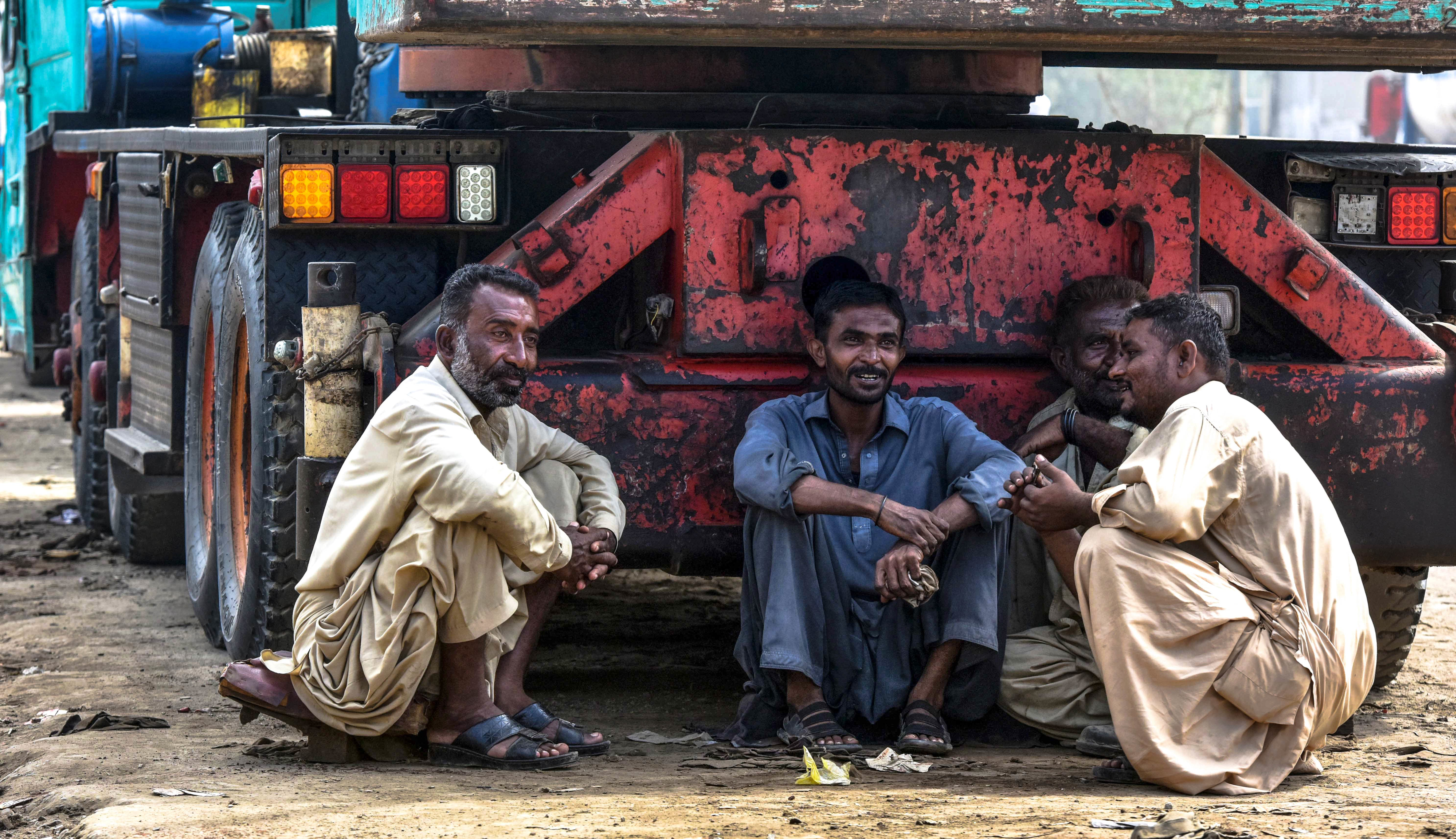 Four labourers sit in the shade of a truck
