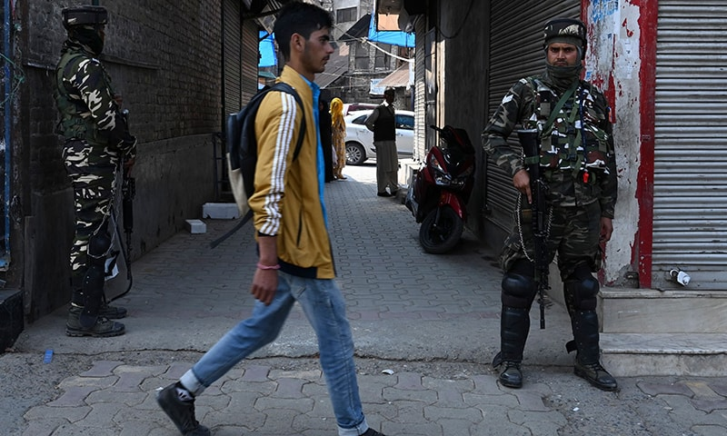 A man walks past as Indian paramilitary troopers stand guard during a lockdown in Srinagar on October 17. — AFP