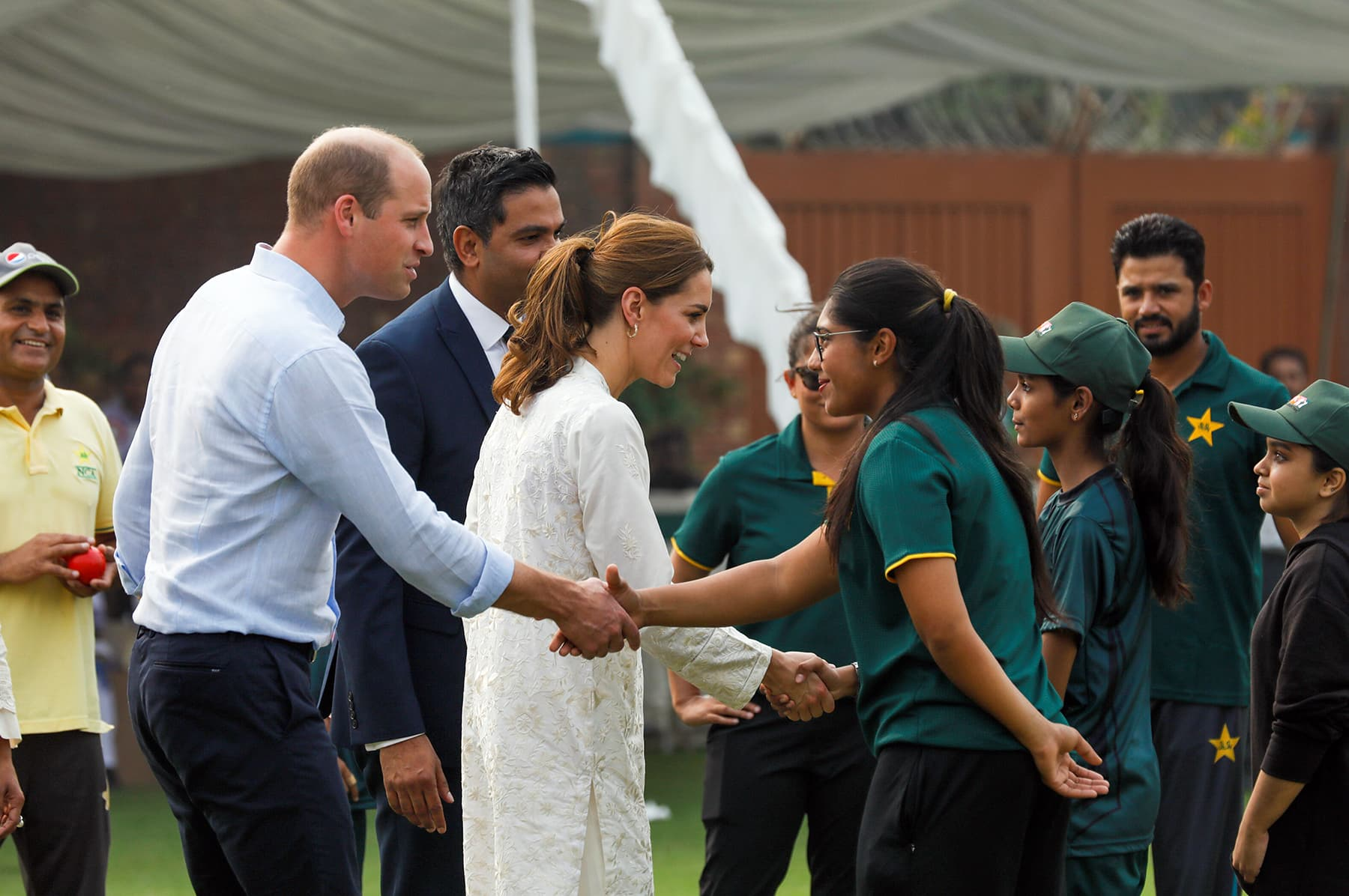 William and Catherine shake hands with children participants of the British Council's DOSTI (friendship) programme at the National Cricket Academy in Lahore October 17. — Reuters