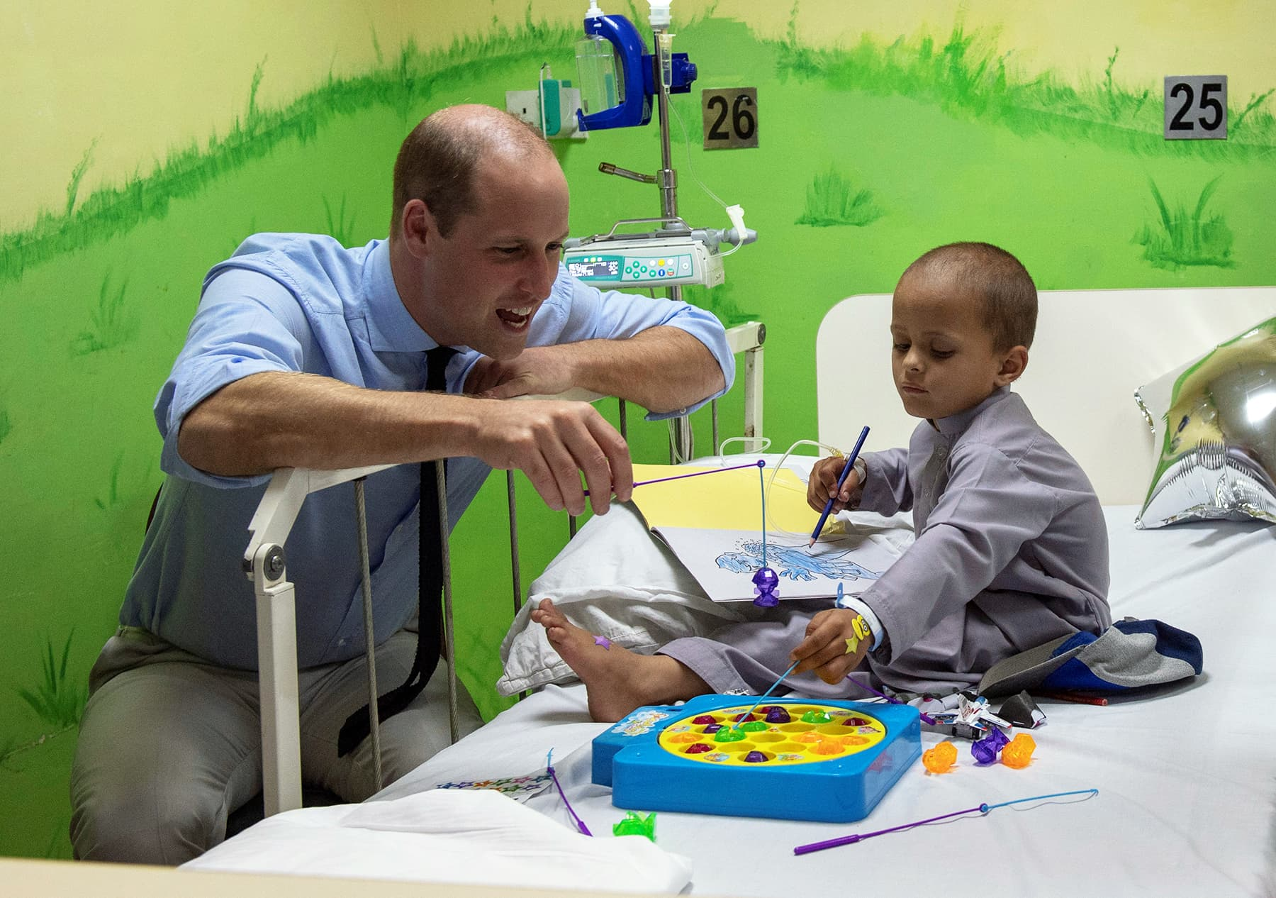 William plays with a young cancer patient at the Shaukat Khanum Memorial Cancer Hospital in Lahore, October 17. — Reuters