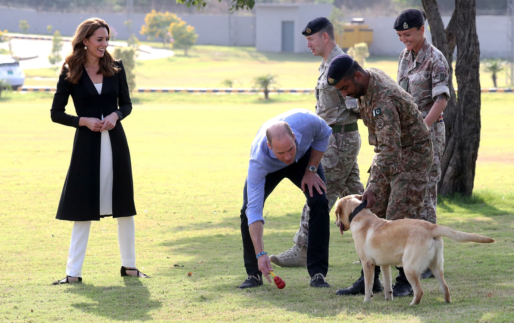 William and Catherine play with golden labrador Polka as they visit an Army Canine Centre, in Rawalpindi, October 18. — Reuters