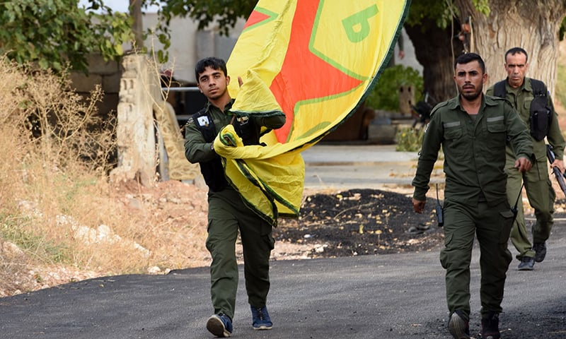 Syrian Kurdish fighters walk carrying a People's Protection Units (YPG) yellow flag in the Syrian Kurdish town of Kobane, also known as Ain al-Arab, along the border with Turkey in the north of Aleppo governorate on Ocotber 18, 2019. — AFP