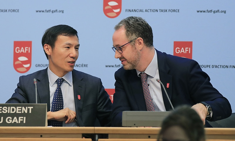 Financial Action Task Force president Xiangmin Liu (left) and executive secretary David Lewis talk to each other after a media conference at the OECD headquarters in Paris on Friday.—AP