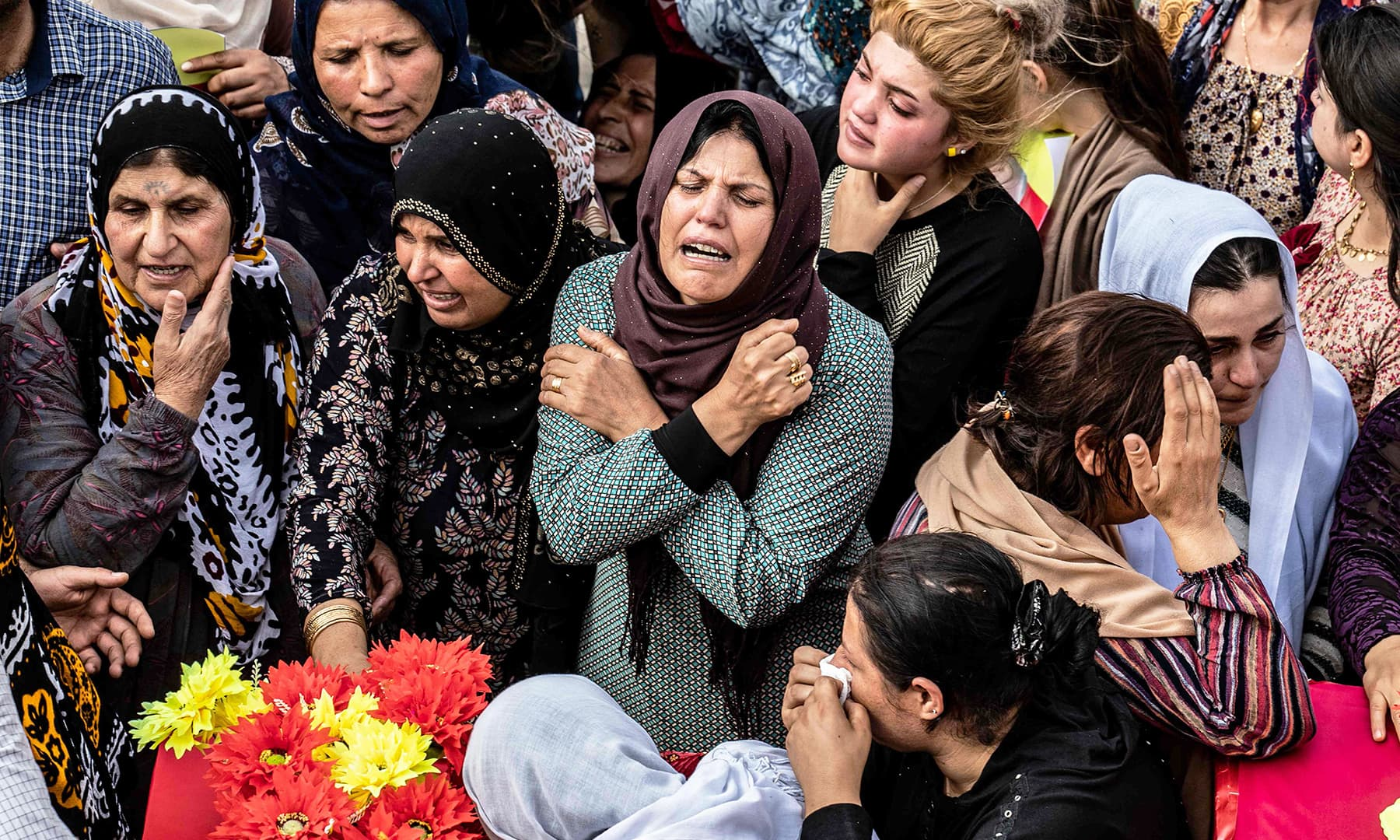 Mourners attend the funeral of civilians and fighters, who died during attacks by Turkish-led forces on the border town of Ras al-Ain, in a cemetary in Tal Tamr, near the Syrian Kurdish town of Ras al-Ain, on Saturday. — AFP