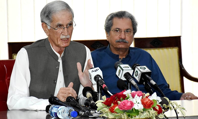 Defence Minister Pervez Khattak flanked by Education Minister Shafqat Mehmood addresses a press conference in Islamabad on Saturday. — PID