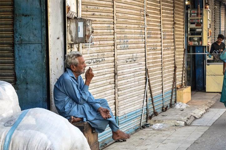 A man smokes outside a closed shop in Boulton Market